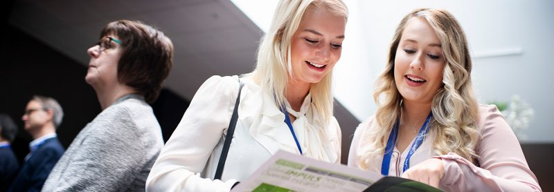 Två tjejer tittar i tidning på IMPULS