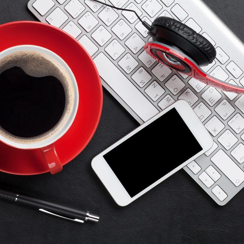 röd kaffekopp, tangentbord och telefon och ett par röda hörlurar