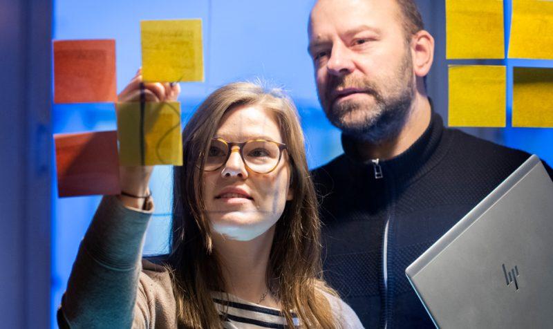 man och kvinna står och tittar på postat-lappar