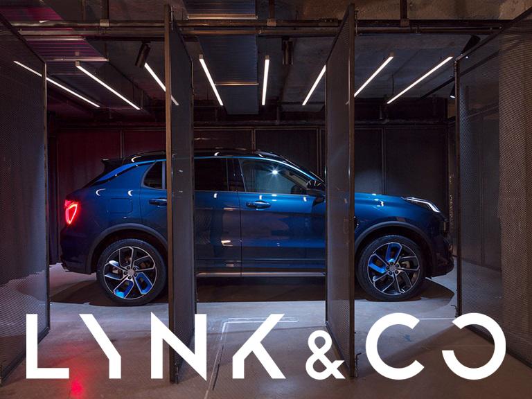 Blå bil i garage med Lynk & Co logo nertill i bilden